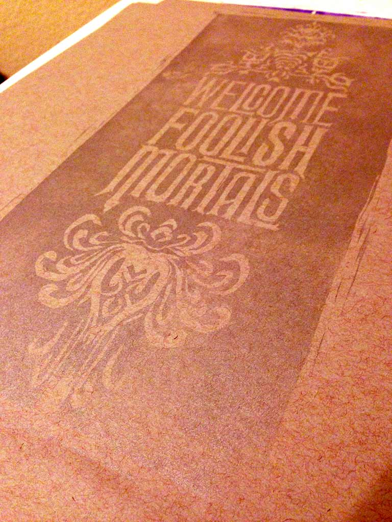 "linoleum block print of ""welcome foolish mortals"""
